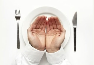 Empty hands over fork, knife and plate.